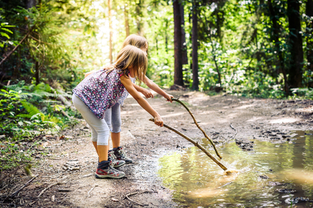 Children hiking in mountains or forest with sport hiking shoes. Girls are playing and learning in the nature with sticks and muddy puddle. Imagens