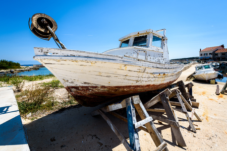 Repair and restoration of old wooden fishing ship or boat. Old weathered fishing boat mounted on wooden jacks for dry dock renovation and repairs with port in background. Adriatic sea - Silba, Croatia