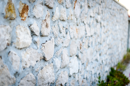 Stone rock fence or gabion and road or footpath. Old built rock wall cement structure in a Mediterranean town in Croatia. Stock Photo