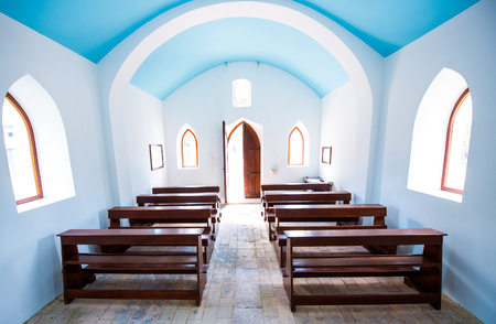 Inside interiors of small generic church. Doors, windows, wooden benches, stone tiles floor and arches of generic village catholic church. Editorial