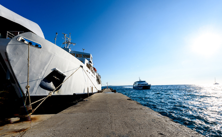 Front loading ferry boat moored with lifted bow at pier. Big ferry boat at the pier and catamaran passenger ship coming into port for disembarkation. Island Silba Croatia. Stock Photo