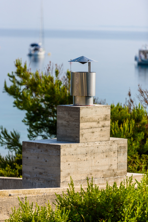 Modern fireplace grill chimney with sea and boats in backgrounds. Contemporary concrete barbecue chimney in Adriatic island.