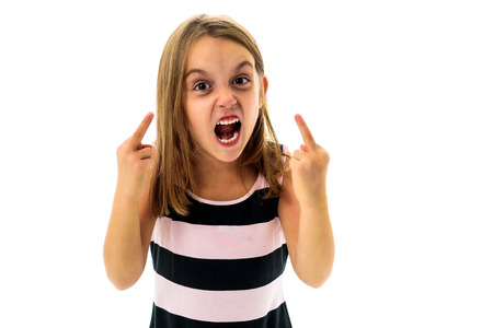 Little young girl is angry, mad, disobedient with bad behaviour. Children making the act of insubordination and disobedience, yelling, flipping off, showing the middle finger. Act of giving the finger. Archivio Fotografico