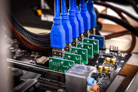 Cryptocurrency mining rig PCIe riser extenders plugged to motherboard. Details of cryptocurrency bitcoin ethereum altcoin graphic card miner mining rig. Stock Photo