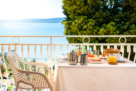 Continental morning breakfast table setting with sea view is served. Hotel restaurant buffet breakfast is served on a balcony near the ocean. Vacation and travelling concept - Portoroz, Slovenia.