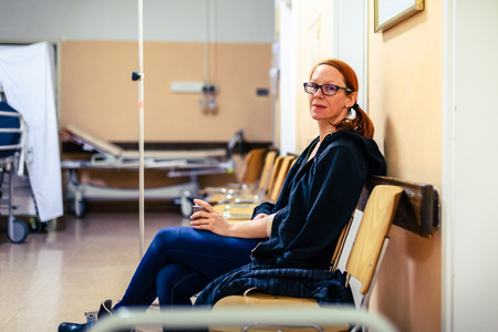 Patient sitting in hospital ward hallway waiting room with iv. Woman with intravenous therapy in her hand is waiting in the clinic corridor with blurred medical personnel in background. 写真素材