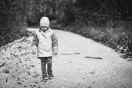 Young sad girl child is walking alone on country road. Abandoned sad little girl is walking in nature and looking down. Concept of loneliness, abandonment, alienation and depression with children. Stock Photo