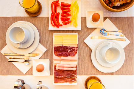 Top view of  continental morning breakfast table setting. Hotel restaurant buffet breakfast is served on vacation and travelling concept. Stock Photo