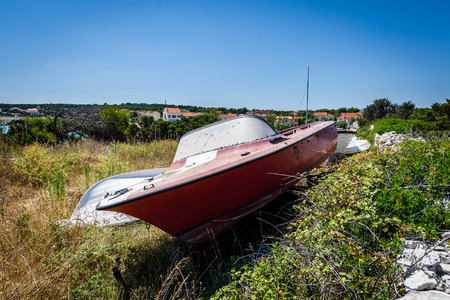 Old abandoned wrecked speed boat at ship or boat graveyard. Lots of different dry docked, destroyed, weathered, old, abandoned boats and ships on the cost of Adriatic sea. Standard-Bild