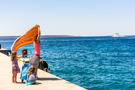 Family and people waiting at turist passenger ferry boat. Mother and twin girls standing on pier with luggage in summertime waving goodbye to ferry boat leaving island Silba to island Premuda, Croatia. Stok Fotoğraf