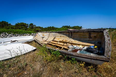 Old abandoned wrecked fishing boat at ship or boat graveyard. Lots of different dry docked, destroyed, weathered, old, abandoned boats and ships on the cost of Adriatic sea.