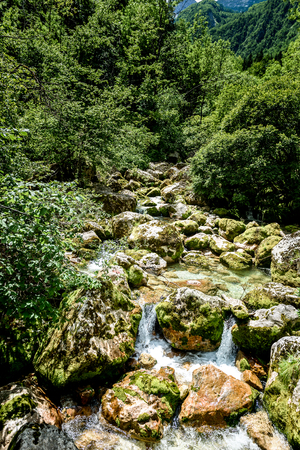 Idyllic mountain river in Lepena valley, Soca - Bovec Slovenia. Heading towards    Sunik water grove of river Lepenca. Beautiful landscape scene with forest, mountains and river in Slovenia, Europe.