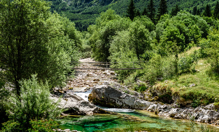 Idyllic mountain river in Lepena valley, Soca - Bovec Slovenia. Bridge over of river Lepenca when heading towards Sunik water grove. Beautiful landscape scene with forest, mountains and river in Slovenia, Europe. Stock Photo