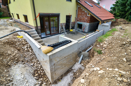 Rebuilding a family house and adding an extension. Setting up a construction site with tools and construction material for residential construction project. Stock Photo