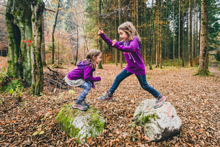 Identical twins are jumping from rocks in forest on hiking. Children in the forest on active trekking in mountains are jumping from rock to rock having fun in Slovenia. Stock Photo