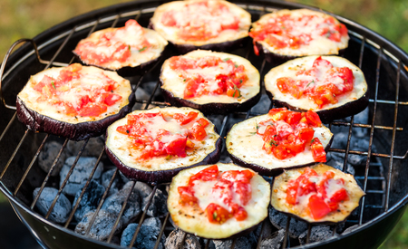 Eggplant with tomato and parmesan cheese on BBQ vegan grill. Grilling vegetables as delicious vegetarian or vegan barbecue picnic over hot coals. Italian style cuisine with fresh vegetable ingredients.