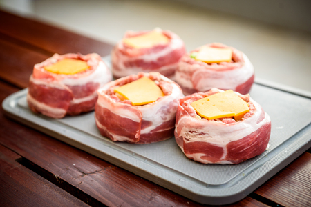 Making home made Beer Can Bacon Burgers on barbecue grill. Preparing stuffed patties, wrapped  in bacon.