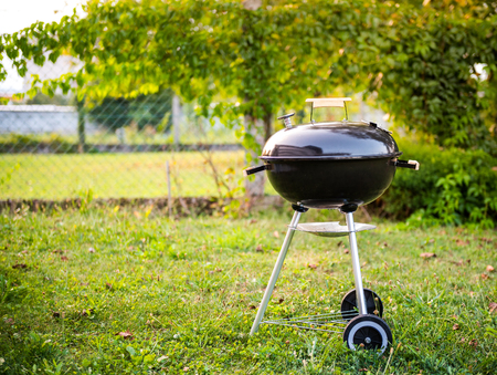 Kettle Charcoal BBQ Barbecue Grill in garden or backyard. Side View of Black Kettle Grill with cover in home front or backyard and green lawn. Portable BBQ Grill for Outdoor Grill Cooking.