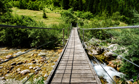 Wooden hanging bridge leading forward over green mountain river. Idyllic mountain river - Lepena valley, Soca – Bovec, Slovenia. Beautiful landscape scene with forest, mountains and river in Slovenia, Europe.