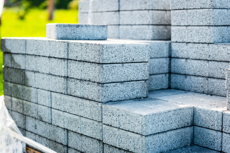 Stack of concrete paving slabs tiles ready for laying pavement. Installing new tiles or slabs at driveway, sidewalk or patio at public or private residence.