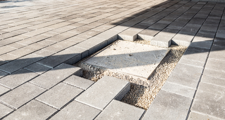 Laying gray concrete paving slabs in house courtyard driveway patio. Installing new tiles or slabs around sewer or canal cover at driveway, sidewalk or patio on leveled foundation base made of sand at public or private residence. Stock Photo