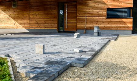 Het leggen van grijze betonnen bestrating platen in de binnenplaats van de oprit van het huis. Professionele arbeiders metselaars plaatsen nieuwe tegels of platen voor oprit, stoep of terras op een vlakke funderingsbasis van zand bij openbare of particuliere woningen.