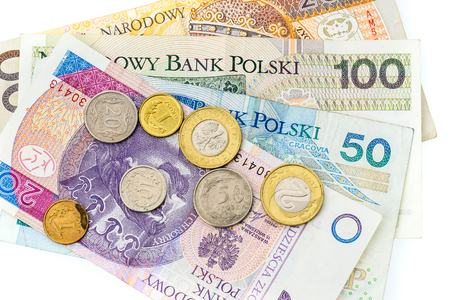 Polish zloty banknotes, money, currency of Poland isolated on white. Different polish paper bills and polish coins laying randomly on white background.