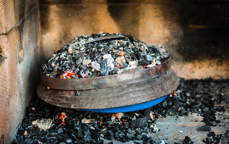 Cooking of traditional Balkan Greek Mediterranean Croatian meal Peka in metal pots called sac sach or sache or a metal lid. Fireplace with open fire and burning coals. Stock Photo