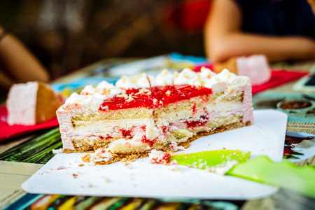 Cutting children birthday cake at kid birthday celebration. Layered cake with ice cream and strawberry is cut at birthday party event with children details in bacfground. Stock Photo