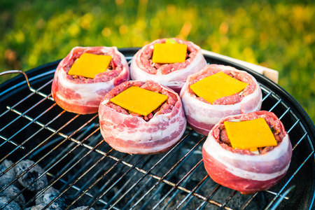 Making home made Beer Can Bacon Burgers on barbecue grill. Preparing stuffed patties, wrapped  in bacon and grilling on indirect heat in nature at back yard BBQ picnic. Low and Slow technique with sunshine in background.
