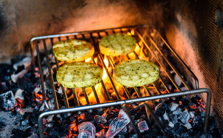 Grilling barbecue cheese over hot coals, fire and flame. Vegetarian bbq grill in professional restaurant fireplace. Backing and barbecuing cheese instead of meat.