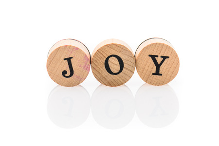 Word Joy from circular wooden tiles with letters children toy. Concept of enjoying spelled in children toy letters. Stock Photo