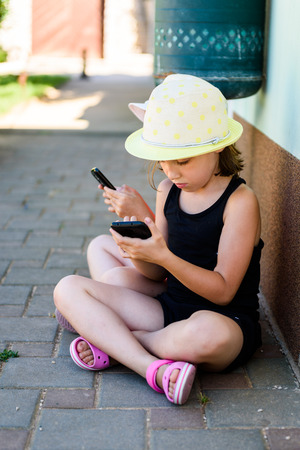Girl child using smartphone for games or internet on vacations. Little girl is playing with smartphone, sitting on paved floor in the shade, wearing sandals and a hat.