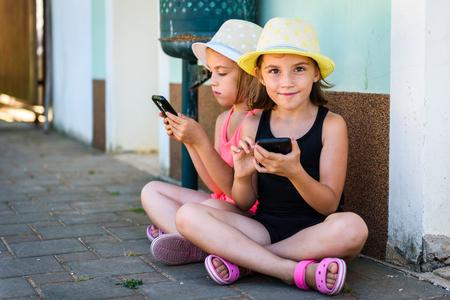 Gemelli identici che usano lo smartphone per i giochi o Internet in vacanza. Bambine, bambini stanno giocando con lo smartphone, seduti sul pavimento lastricato all'ombra, indossando sandali e un cappello. Archivio Fotografico
