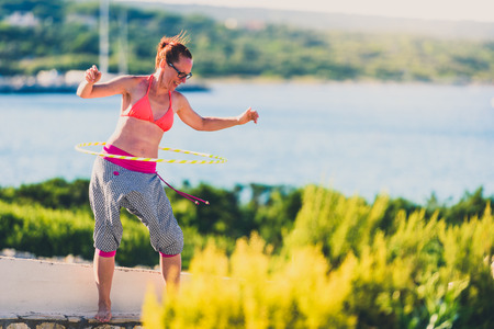 Attractive adult woman is playing with hula hoop in nature. Young, healthy, active hipster woman is hula hooping on the sea side with view of blue sea and boats in summer sunny day in Silba, Croatia.