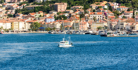 Panoramic view of Mali Losinj port and city in Croatia. Fishing boat is leaving the port with many other boats, sail ships and old town buildings.in the background.