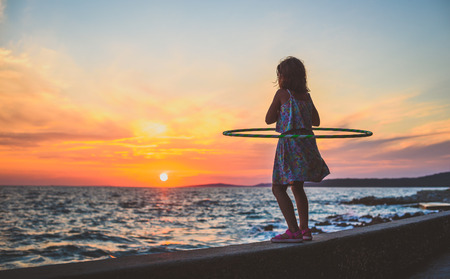 Girl is watching amazing sea sunset with hula hoop. Child is enjoying the sunset hooping, exercising and being active on a beach of island Silba in Croatia. Concept of healthy lifestyle in nature.