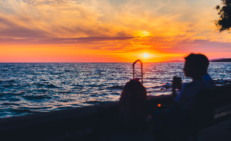 Amazing golden summer sunset in Adriatic sea, Silba, Croatia. Silhuete of intentionally out of focus people watching and enjoying beautiful sunset over the ocean.
