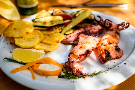 Grilled squid with potato chips, vegetables on a white plate. Traditional Mediterranean Croatian dish in Croatian restaurant on wooden table.