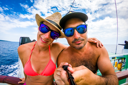 Happy Couple in love, enjoying the summer by the sea. Husband and wife making selfie photo with phone on a Ferry Boat, Yacht or cruise ship in Croatia.
