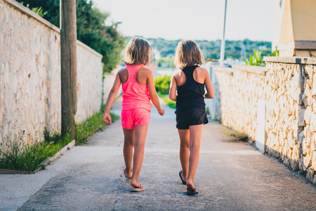 Identical twin girls sisters walking the island streets of Croatia. Children on summer vacation are waliking towards the beach through narrow Mediterranean streets of small island Silba, Croatia. Stock fotó
