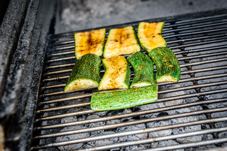 Grilling zucchini or courgette on a coal barbecue grill. Traditional Mediterranean healthy dish in prepared in barbecue fireplace. Stock Photo