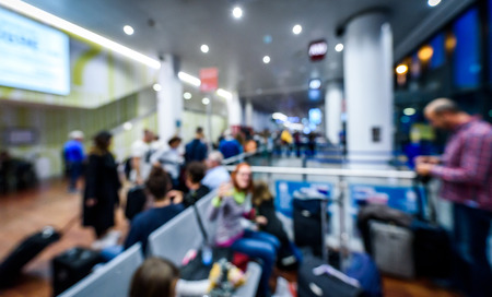 Abstraktes verschwommenes Bild von Passagieren, die auf dem Flughafen warten. Überfüllter Flughafenterminal mit defokussierter Menge, die auf kommerziellen Flugzeugflug im Flughafen Milano Bergamo wartet. Standard-Bild