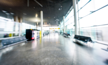 Abstract blurred picture of passengers waiting on the airport. Empty defocused airport terminal with  waiting space for commercial aeroplane flight in Santiago de Compostela airport.