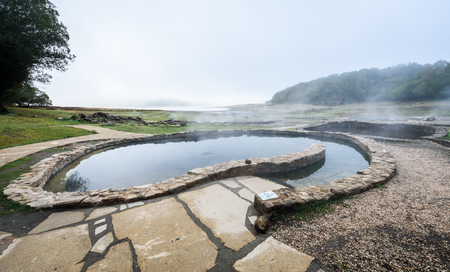 Natural Roman baths outdoors with hot steam and thermal water. Old roman hot springs open air spa and hot natural thermal water in small pools and stone bathtubs. Aquis Querquennis Bande Galicia Spain