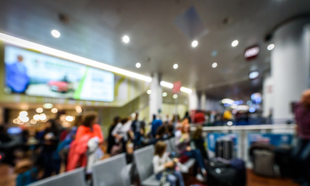Abstract blurred picture of passengers waiting on the airport. Crowded airport terminal with defocused crowd waiting commercial aeroplane flight in Milano Bergamo airport.