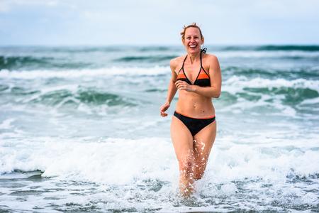Frau, die das Meer und die Wellen des Atlantiks genießt. Reife, junge attraktive Frau mittleren Alters im Badeanzug Bikini läuft im Ozean Meer, spielt und spritzt das Wasser. Atlantik - Portugal.
