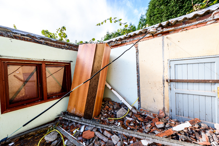 Ruins of old abandoned family house destroyed in natural disaster. Demolished house before construction works of rebuilding and renovating old real estate. Stockfoto