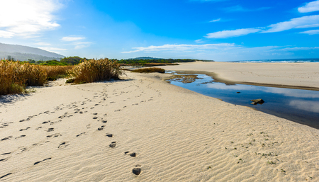 Footsteps tracks on sandy beach in Portugal Atlantic coast. Tracks in the sand with the ocean in the background. Atlantic ocean, Afife beach, Portugal. Background wallpaper picture. Stock Photo