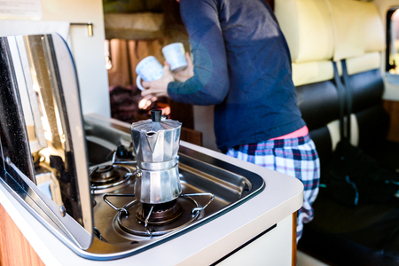 Cooking coffee in campervan, caravan or RV on camping trip. Woman is making coffee in the morning using italian kafetiera on a family vacation camping trip.